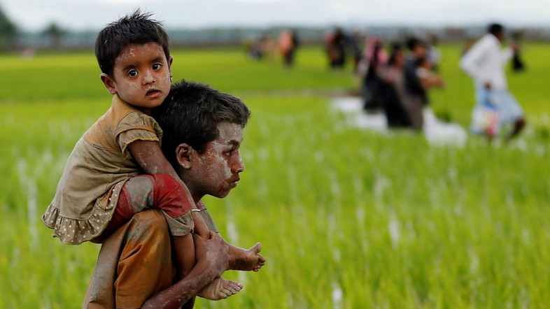 A Rohingya boy carries a child after after crossing the Bangladesh-Myanmar border in Teknaf, Bangladesh, September 1, 2017. REUTERS/Mohammad Ponir Hossain - RC1AE87D0700